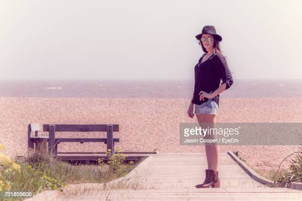portrait of young woman standing on beach against clear sky - aldeburgh stock photos and pictures