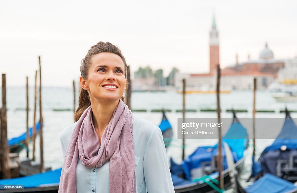 portrait of young woman standing on embankment in venice, italy : Stock Photo