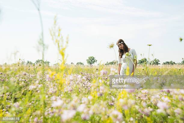 Portrait of young woman standing on flower meadow