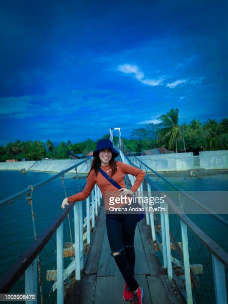 portrait of young woman standing on footbridge against sky - malabon stock pictures, royalty-free photos & images
