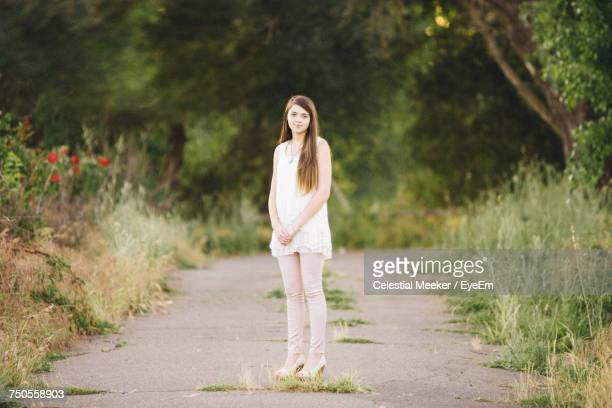 portrait of young woman standing on footpath amidst grassy field - one teenage girl only stock pictures, royalty-free photos & images