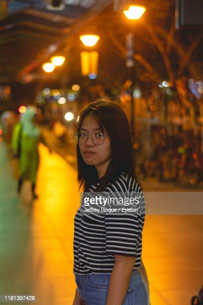 portrait of young woman standing on footpath in city at night - jeffrey roque stock photos and pictures