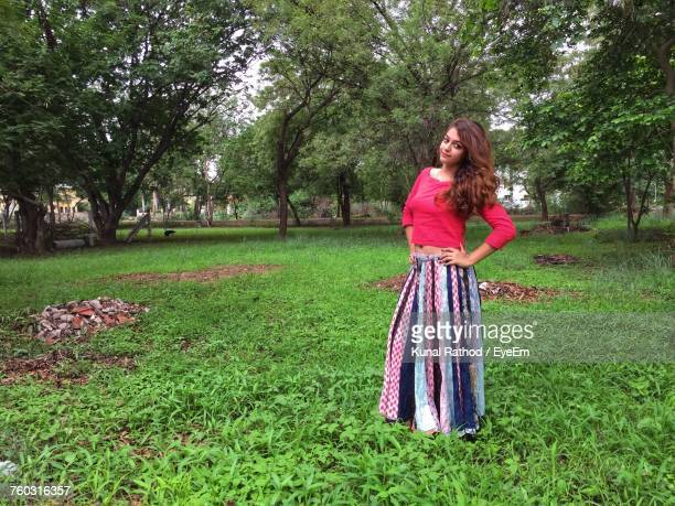 Portrait Of Young Woman Standing On Grassy Field At Park