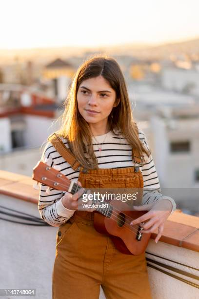 portrait of young woman standing on roof terrace in the evening playing ukulele - ukulele stock-fotos und bilder