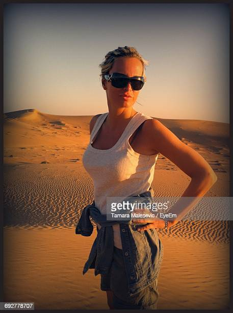 Portrait Of Young Woman Standing On Sand Dunes At Desert