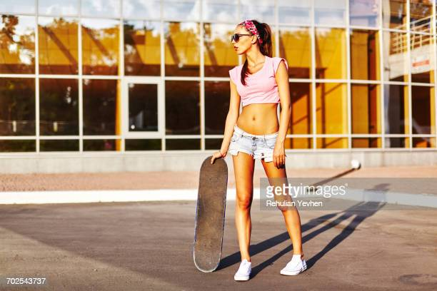 portrait of young woman standing outdoors, holding skateboard - クロップトップ ストックフォトと画像