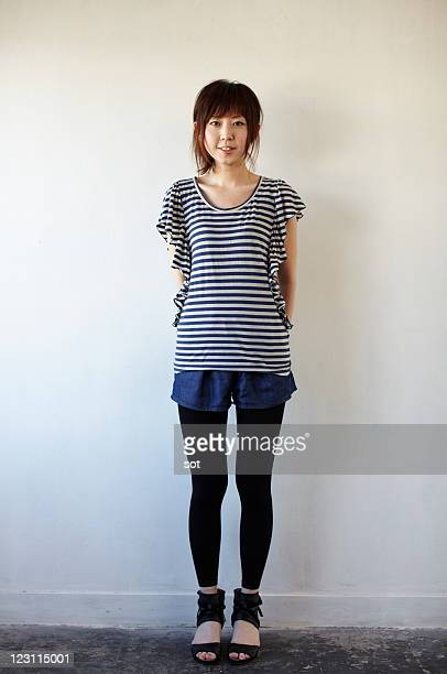 portrait of young woman standing - striped shirt stock pictures, royalty-free photos & images