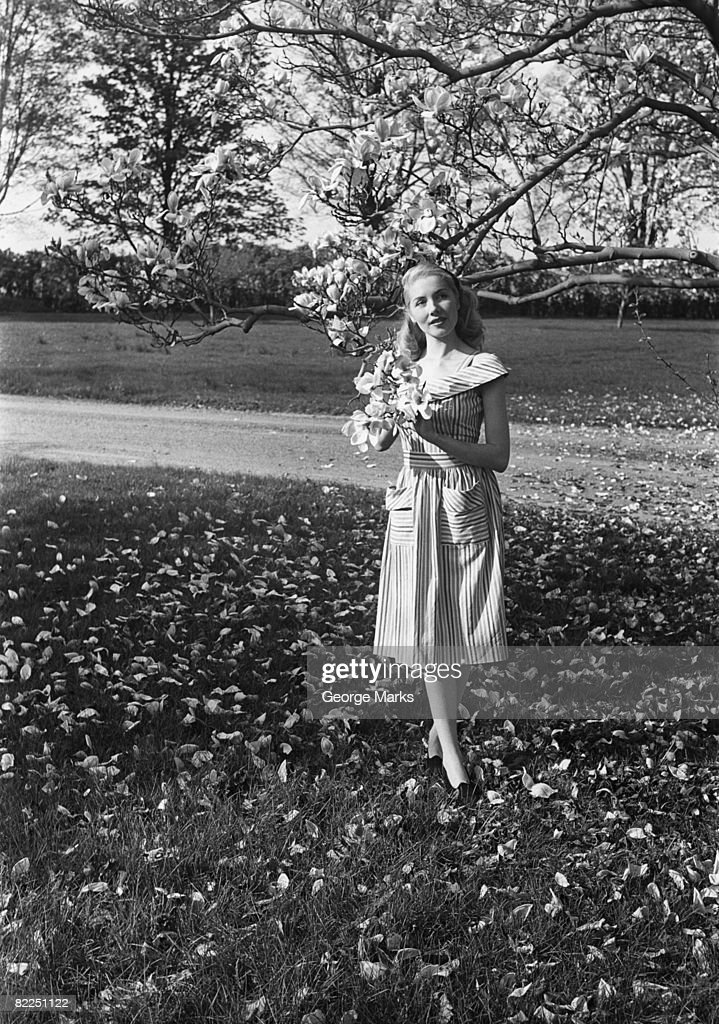 Portrait of young woman standing under magnolia tree in park : Stock Photo
