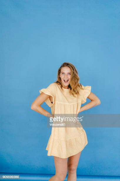 portrait of young woman standing wearing a dress - main sur la hanche photos et images de collection