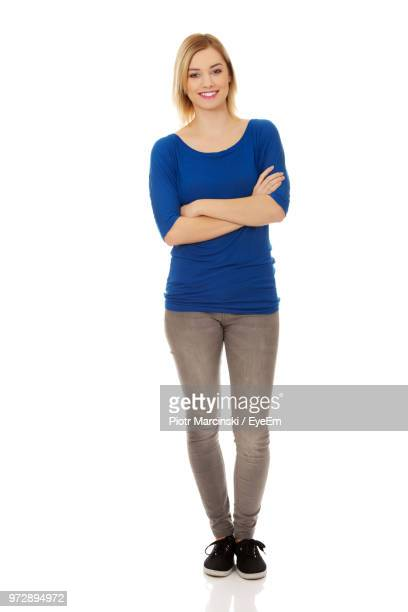 portrait of young woman standing with arms crossed against white background - stare in piedi foto e immagini stock