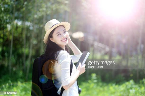 portrait of young woman standing with book in park - 女子大生 ストックフォトと画像