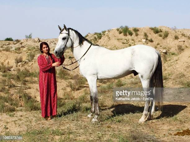 portrait of young woman standing with horse on field - turkmenistan stock pictures, royalty-free photos & images