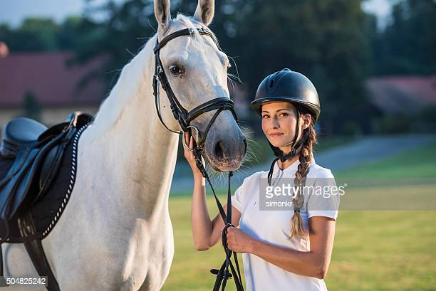 portrait of young woman standing with horse - riding hat stock pictures, royalty-free photos & images