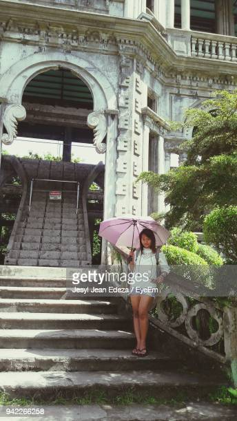 Portrait Of Young Woman Standing With Umbrella On Steps Against Building