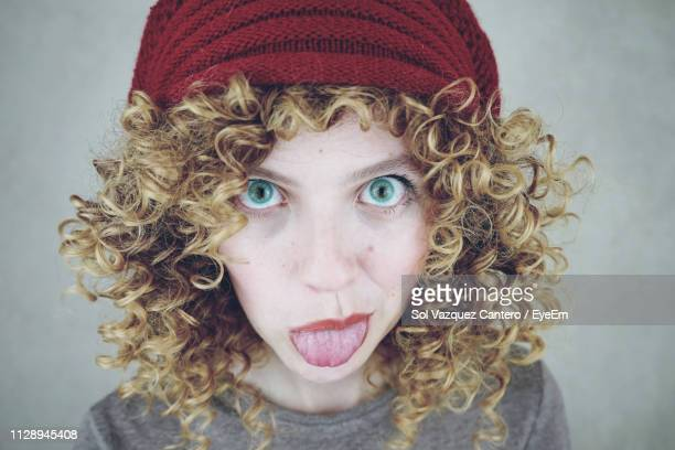 portrait of young woman sticking out tongue against gray background - frizzy stock pictures, royalty-free photos & images