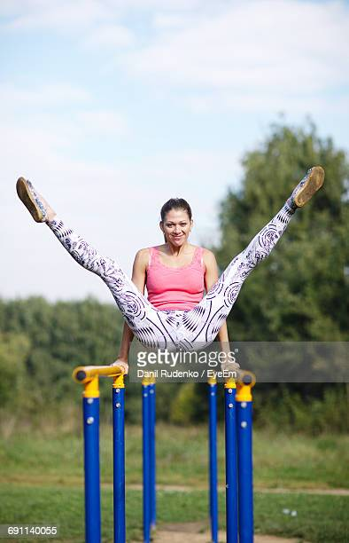 Portrait Of Young Woman Stretching On Parallel Bars In Park