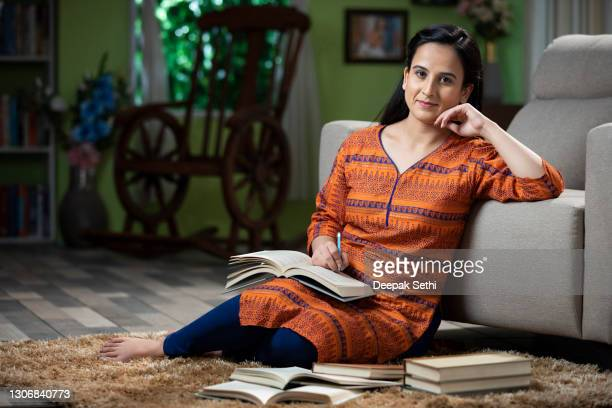 portrait of young woman student sitting on floor in a room reading books:- stock photo - hand on chin stock pictures, royalty-free photos & images