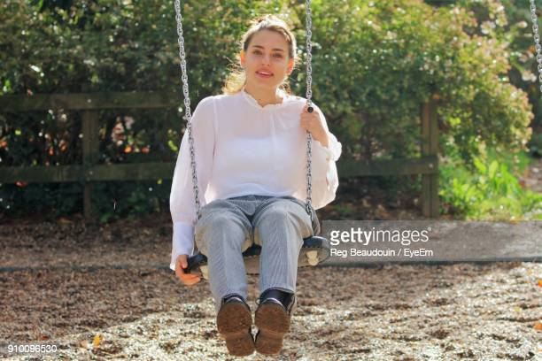Portrait Of Young Woman Swinging During Sunny Day
