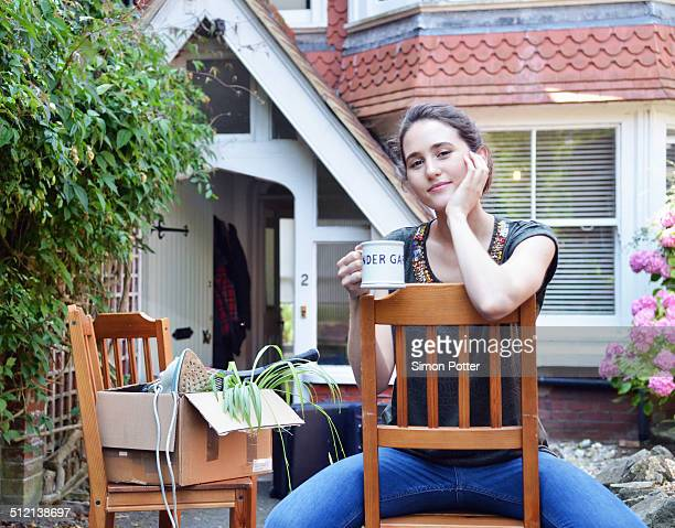 Portrait of young woman taking a coffee break outside new house