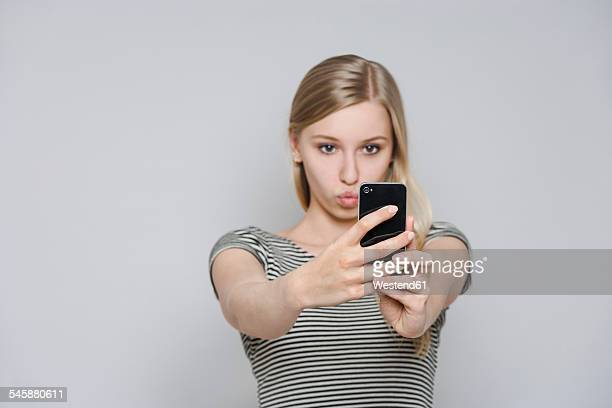 Portrait of young woman taking a selfie with smartphone