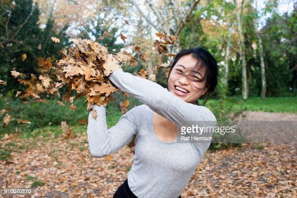 Portrait of young woman throwing dry leaves while standing at park during autumn