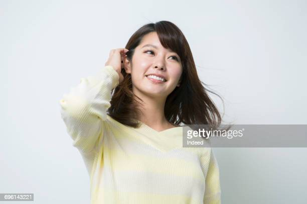 portrait of young woman, touching her hair - 髪に手をやる ストックフォトと画像