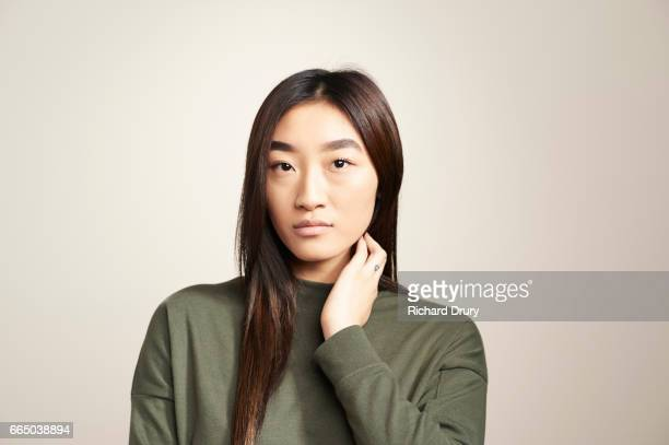 portrait of young woman touching neck - uncertainty stock pictures, royalty-free photos & images