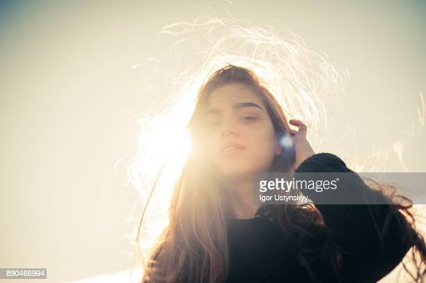 portrait of young woman tucking the hair behind the ear - tegenlicht stockfoto's en -beelden