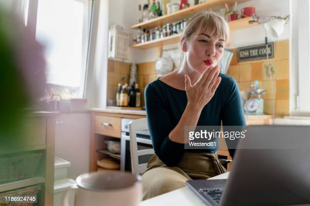 portrait of young woman using laptop in the kitchen, blowing a kiss - voip stockfoto's en -beelden