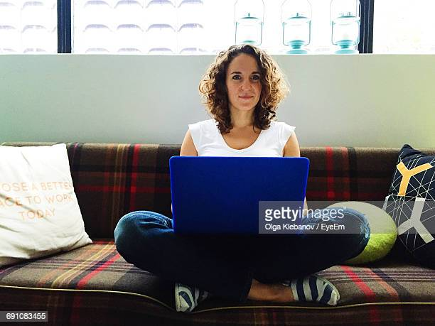 Portrait Of Young Woman Using Laptop While Sitting On Sofa At Home