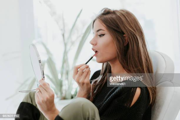 portrait of young woman using lip pencil - lip liner stock photos and pictures
