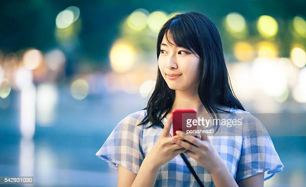Portrait of young woman using phone on street at night