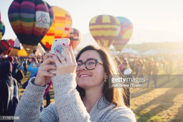 portrait of young woman using smart phone - balloon fiesta stock pictures, royalty-free photos & images