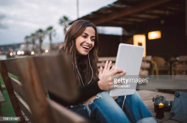 Portrait of young woman using tablet with earphones