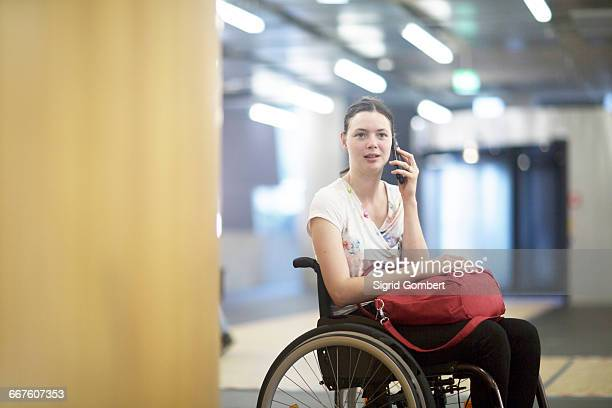portrait of young woman using wheelchair talking on smartphone - sigrid gombert stock pictures, royalty-free photos & images