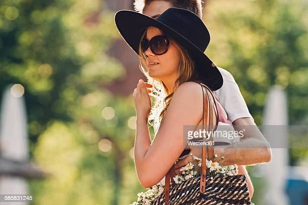 Portrait of young woman walking arm in arm with her boyfriend