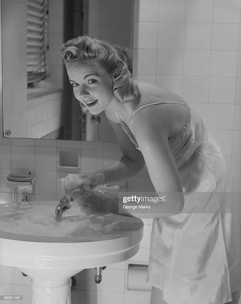 Portrait of young woman washing hands in bathroom sink : Stock Photo