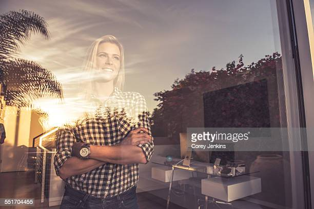 Portrait of young woman watching sunset from suburban window