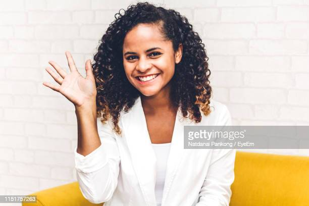 portrait of young woman waving against white wall - waving stock pictures, royalty-free photos & images