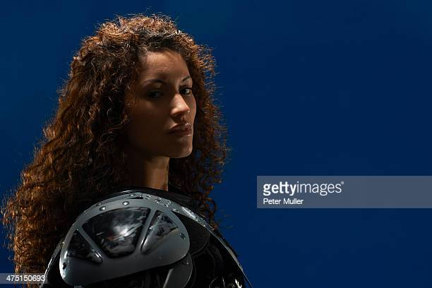 Portrait of young woman wearing american football shoulder pads