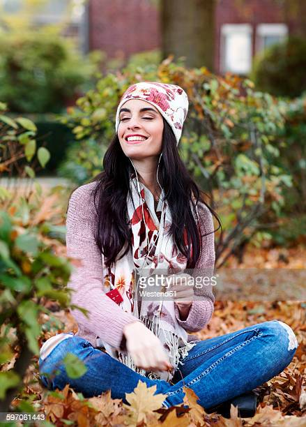 Portrait of young woman wearing autumn fashion hearing music with earphones