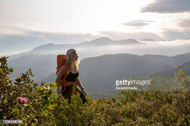 portrait of young woman wearing backpack, at sunrise - liguria foto e immagini stock