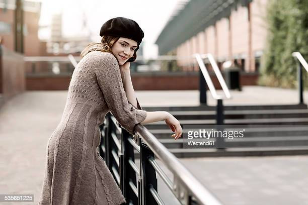 portrait of young woman wearing beret and knitted dress leaning on a railing - ニットワンピース ストックフォトと画像