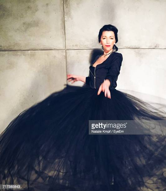 portrait of young woman wearing black gown against wall - evening gown stock pictures, royalty-free photos & images