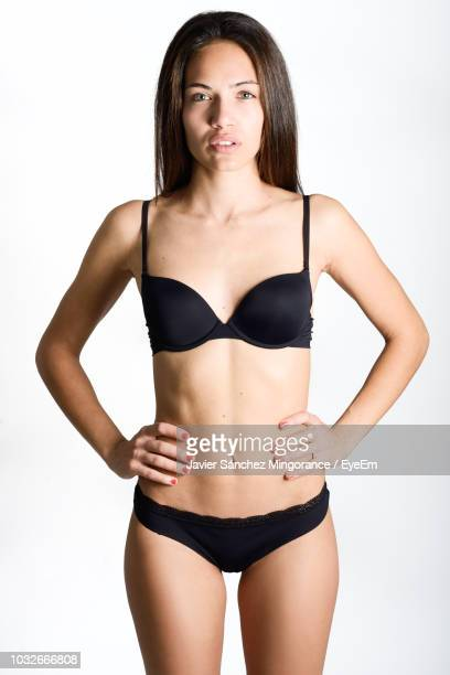 Portrait Of Young Woman Wearing Black Lingerie Standing Against White Background