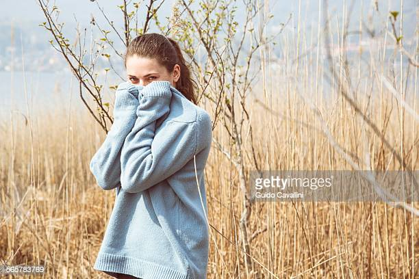 Portrait of young woman wearing blue sweater on lakeside, Lake Mergozzo, Verbania, Piemonte, Italy