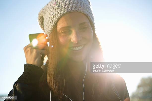 Portrait of young woman wearing earphones listening to music