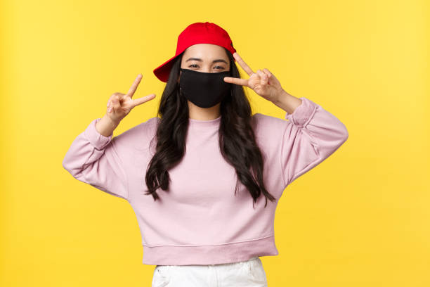 Portrait of young woman wearing eye mask against yellow background