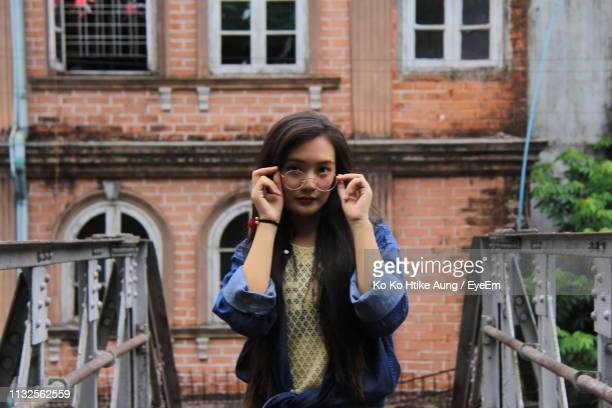 portrait of young woman wearing eyeglasses while standing against building - ko ko htike aung stock pictures, royalty-free photos & images
