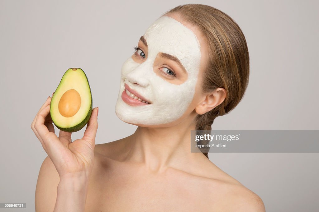 Portrait of young woman wearing face mask, holding avocado : Stock Photo
